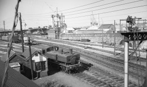 3. Dock St 1963 In this view from Octopus Bridge, the Dock Street pilot, 0-6-0 PT No. 1656, waits outside the Dock St Goods Yard ground frame, sited at the entrance to the yard. The photograph is undated but, in the background, the erection stage of George Street Bridge confirms that it is sometime during 1963. East Dock St signal box, in the distance, and other boxes in the immediate area closed on 25 January 1960, all lines then being controlled by a new Dock St box sited just out of picture to the right. M.R.S Collectio